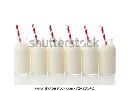 Row of filled glass milk bottles with retro red and white drinking straws on a white background - stock photo