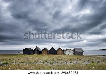 Row of fishing shacks on the Baltic Sea under a dramatic cloudy sky. Location: Faro Island, Sweden - stock photo