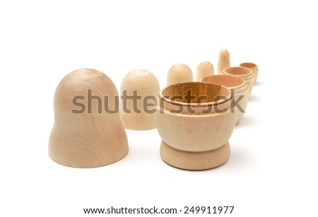 Row of five disassembled wooden matryoshkas on white background - stock photo