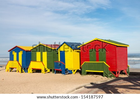 Row of four colorful beach huts by sea at Gordons Bay near Cape Town South Africa - stock photo