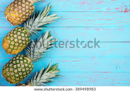 Row of four slanted pineapple fruits laid down on old blue wooden floor or table with copy space - stock photo