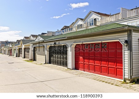 Row of garage doors at parking area for townhouses - stock photo