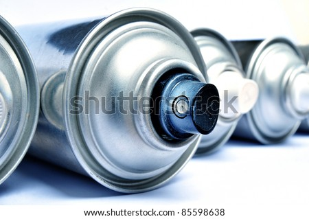 Row of graffiti aerosol cans - Blue toned - stock photo