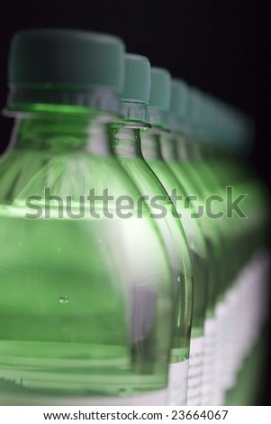 Row of green bottles of sparkling water, with shallow depth of field. The second bottle is in focus. - stock photo