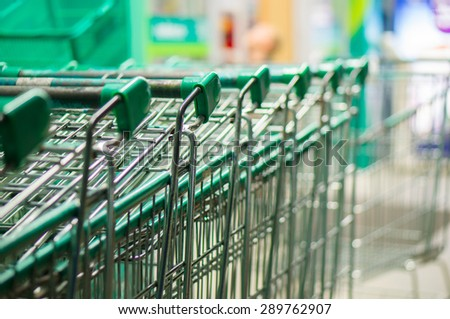 Row of green shopping carts in front of entrance to supermarket - stock photo