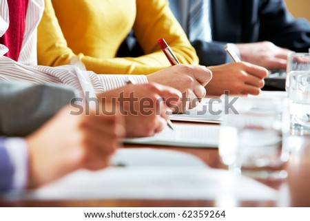 Row of hand holding pen and writing something during lecture - stock photo