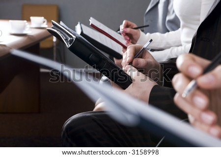Row of hands filling in a form - stock photo