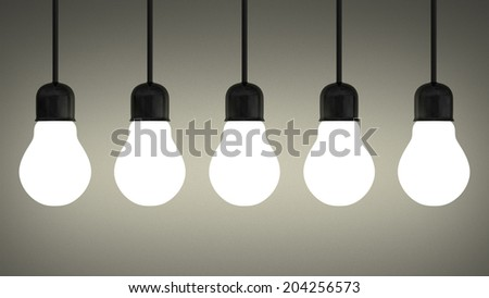 Row of hanging glowing tungsten light bulbs on gray textured background - stock photo