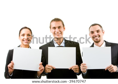 Row of happy business partners holding blank papers and looking at camera - stock photo