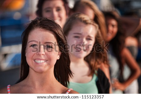 Row of happy smiling female teenagers outdoors - stock photo