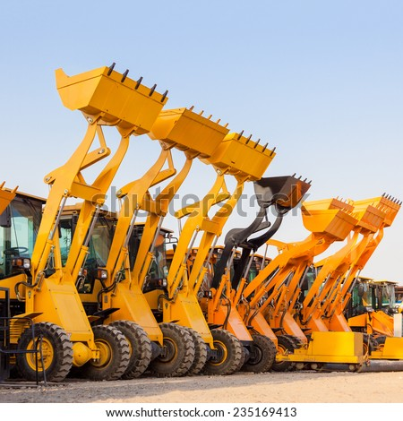 Row of heavy construction excavator machine  against blue sky in a construction site. - stock photo