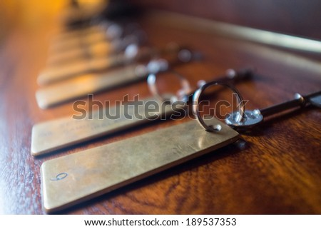 Row of Hotel keys with metal tags. Shallow DOF - stock photo