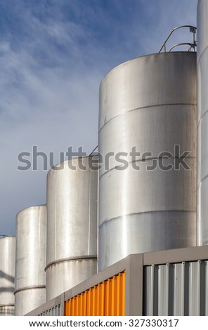 Row of huge petrol oil tanks in refinery industry with beautiful blue sky. - stock photo