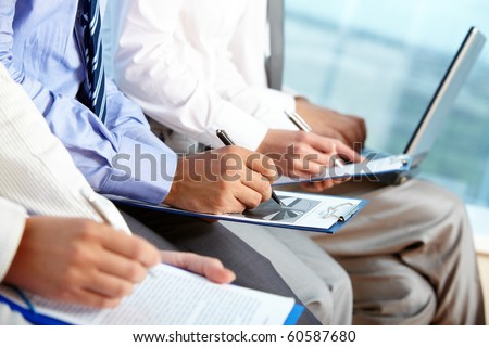 Row of human hands over papers making notes at conference - stock photo