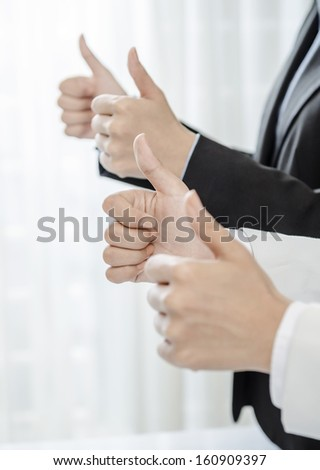 Row of human hands showing thumb up - stock photo