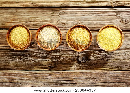 Row of individual bowls containing couscous, bulgur, millet and quinoa viewed from above on old rough rustic wooden boards depicting a healthy diet of grains and cereals - stock photo