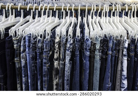 Row of Jeans and trousers on hangers for sale. - stock photo
