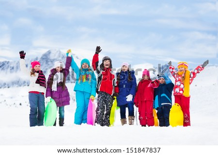 Row of large group of kids, friends, boys and girls standing together outside in snow and waiving hands - stock photo