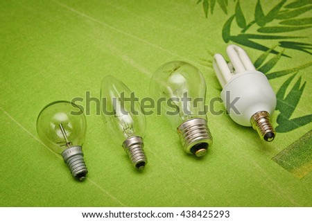 Row of light bulbs on green background  - stock photo