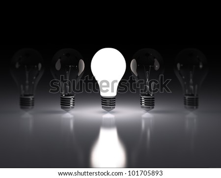 row of light bulbs one lit - stock photo