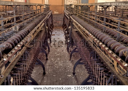 Row of looms in an old silk mill factory, in light HDR processing - stock photo
