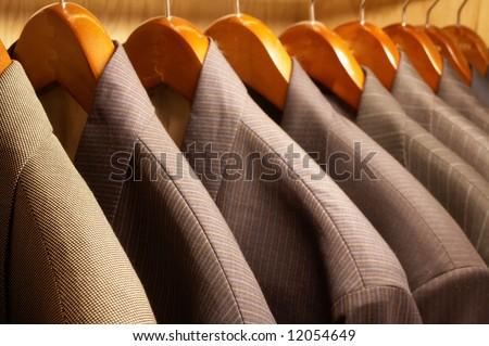 Row of men's suit jackets hanging on hangers - stock photo
