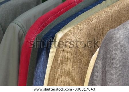Row of men suit jackets on hangers - stock photo