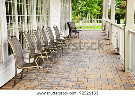 Row of metal chairs on brick patio against windows - stock photo