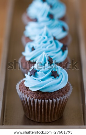 Row of miniature chocolate cupcakes decorated with stars - stock photo