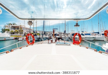 Row of moored yachts and boats in a harbor, view from the yacht deck - stock photo