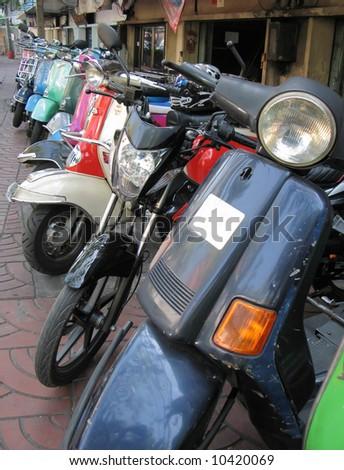 Row of mopeds on a street of Bangkok - stock photo