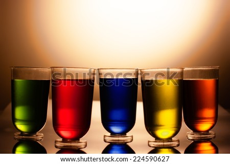 Row of multicolored alcohol drinks in shot glasses - stock photo