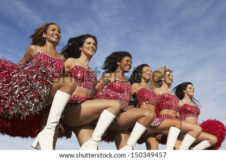 Row of multiethnic cheerleaders doing high kick against cloudy sky - stock photo