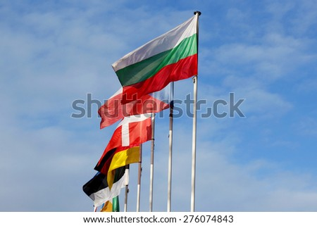 Row of national flags against blue sky - stock photo