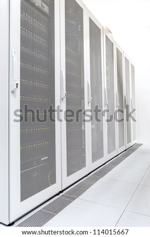 Row of network servers in datacenter room - stock photo