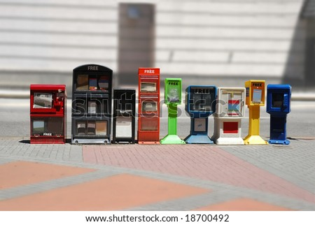 Row of news stands (newspaper dispensers) beside a street by a sidewalk - stock photo