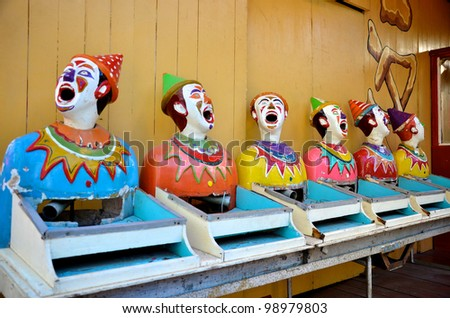 Row of old laughing clowns at an amusement park - stock photo