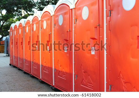 Row Of Orange Color Portable Toilets - stock photo