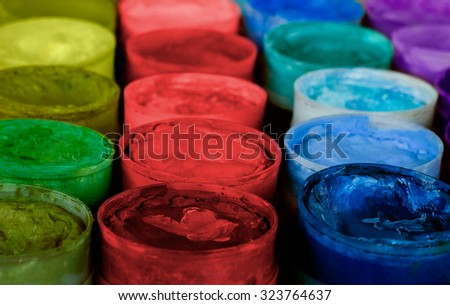 Row of paint pots in a variety of colors, most of which are primary. The pots have seen lots of use, perhaps by a very creative person. - stock photo