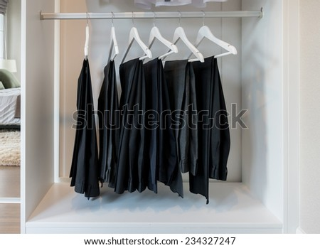 row of pants hanging on coat hanger in white wardrobe - stock photo