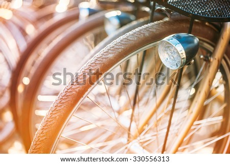 Row of parked vintage bicycles bikes for rent on sidewalk. Bike Bicycle Parking In European City. Close up of wheel and bicycle headlight - stock photo