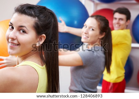 Row of people holding balls in sport club - stock photo