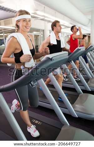 Row of people working out on treadmills at the gym - stock photo