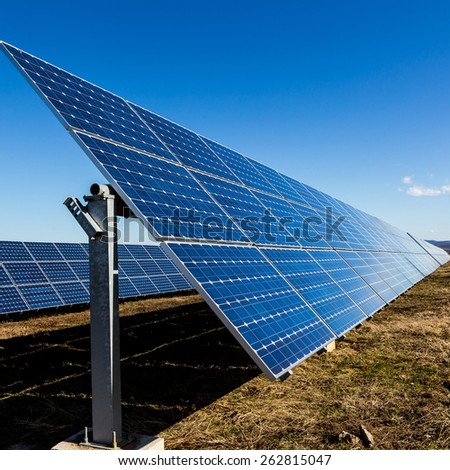 Row of photovoltaic solar panels in fields of countryside - stock photo