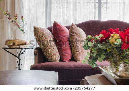 row of pillows on red sofa with flower in foreground at home - stock photo