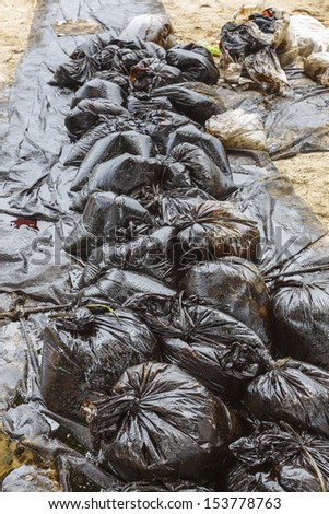 Row of Plastic bags which contain crude oil from the clean up operation on oil spill accident on Ao Prao Beach at Samet island on July 2013 in Rayong, Thailand. - stock photo