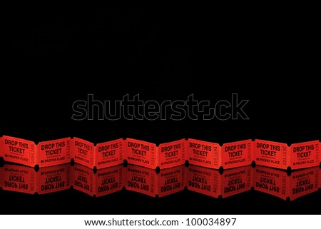 Row of red tickets on a black reflective surface - stock photo