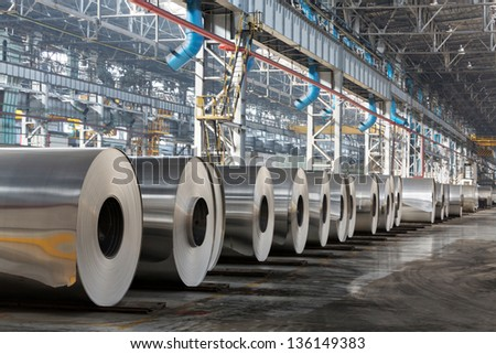 Row of rolls of aluminum lie in production shop of plant. - stock photo