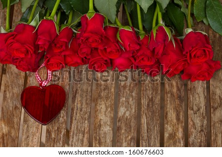 row of roses with  red  heart  on wooden  table - stock photo