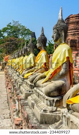 Row of ruined statue of buddha at Wat Yai Chaimongkol, Ayuthaya, Thailand. - stock photo